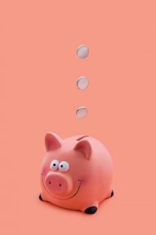 Rosa sparschwein mit den münzen, die unten fallen