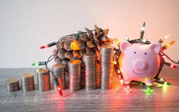 Rosa sparschwein mit münzen stapeln wachstumsdiagramm und partylichter, sparen sie geld für zukünftige investitionspläne und pensionsfondskonzept.