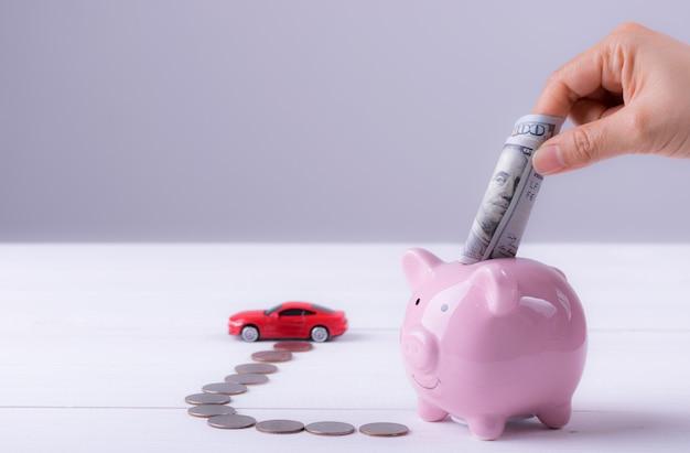 Rosa sparschwein, münzen, auto. frauenhand, die dollarbanknote zum sparschwein für neuwagen setzt.