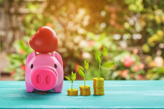 Rosa sparschwein über münzen stapeln und sparen geldkonzept.