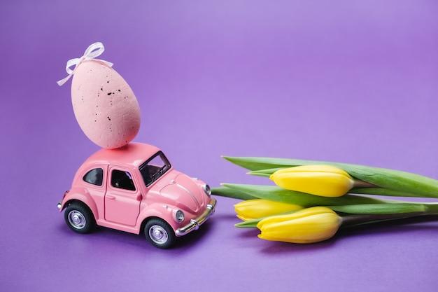 Rosa spielzeug retro auto mit einem ei auf dem dach und gelben tulpen auf einer lila oberfläche