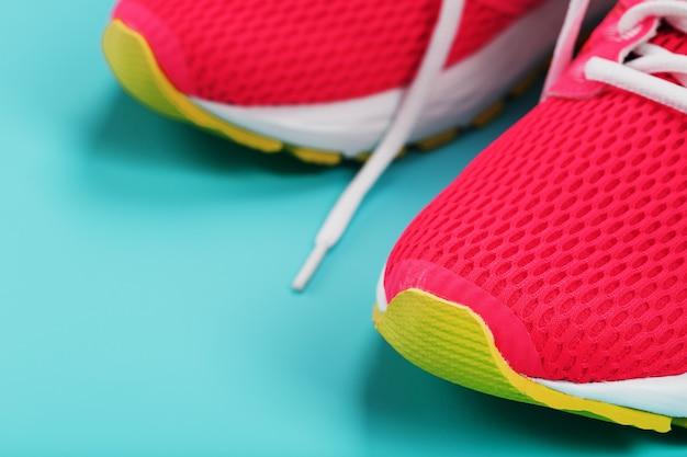 Rosa sportschuhe für das laufen auf einem blauen hintergrund mit freiem raum. draufsicht, minimalistisches konzept