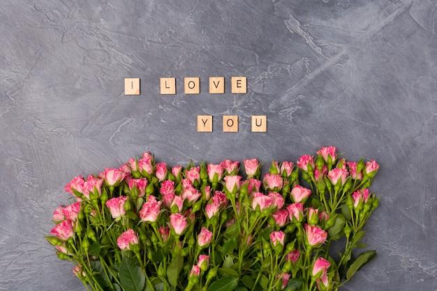 Rosa sprayrosen und ich liebe dich buchstaben auf grauem hintergrund. ansicht von oben. valentinstag-konzept der frauen tagesmutter
