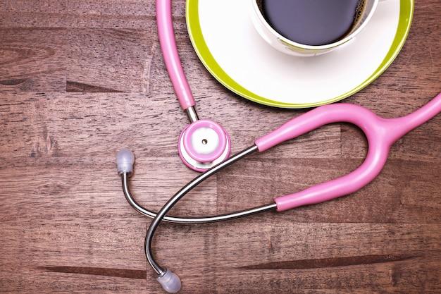 Rosa stethoskop und eine tasse kaffee