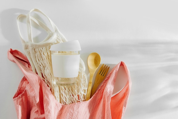 Rosa stoff-einkaufstasche mit netz-markttasche, bambusbesteck und wiederverwendbarer kaffeetasse.