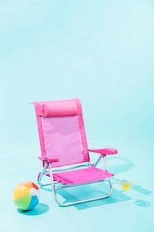 Rosa strandkorb, bunter strandball und gelbes getränk in elegantem glas auf hellblauem hintergrund
