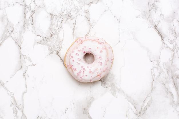 Rosa süße donuts auf einer marmorhintergrundansicht von oben