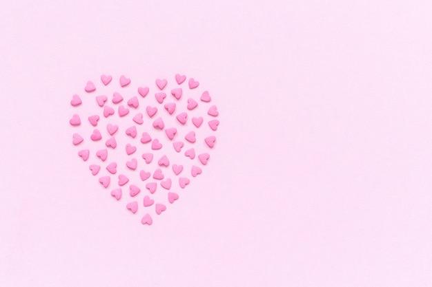 Rosa süßigkeiten besprüht in der herzform auf rosa pastellhintergrund