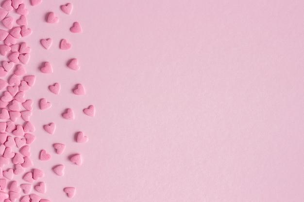 Rosa süßwarenherzen gelegen auf der linken seite auf rosa hintergrund, grußkarte