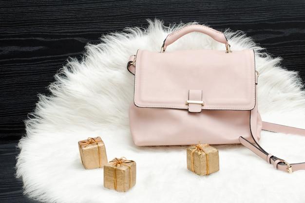 Rosa tasche und geschenkbox auf weißem pelz
