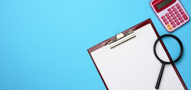 Rosa taschenrechner, ordner mit leeren weißen blättern und schwarzer lupe auf einer blauen oberfläche. banner für unternehmen, draufsicht