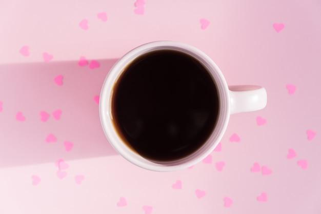 Rosa tasse mit heißem schwarzen tee auf rosa hintergrund mit verstreuten papierherzen. liebes- und pflegekonzept.