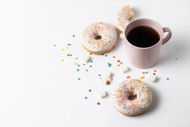 Rosa tasse mit kaffee oder tee und frischen leckeren donuts, süße bunte dekorative süßigkeiten auf weißem hintergrund. bäckereikonzept, frisches gebäck, leckeres frühstück, fast food.