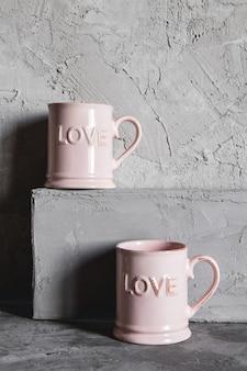 Rosa tassen mit liebe, grauer hintergrund. konzept der romantischen begegnung, liebe, romantisches frühstück