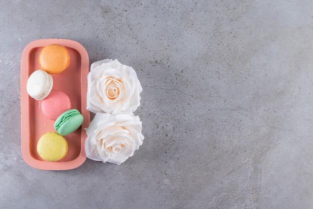 Rosa teller der süßen mandelkuchen mit weißen rosen auf steinernem hintergrund.