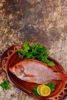 Rosa tilapia-fisch mit kräutern und zitrone auf tablett. nahansicht.