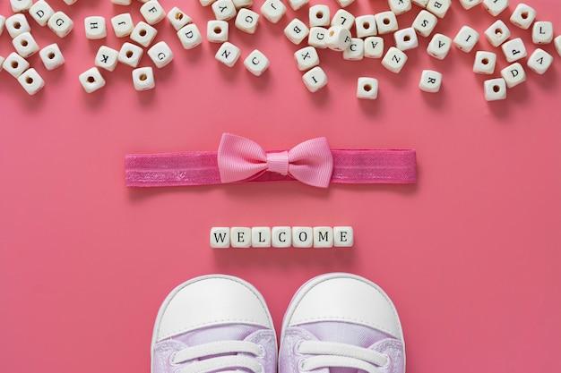 Rosa tisch des mädchens mit neugeborenen schuhen, bogen und begrüßungswörtern. baby flach lag.