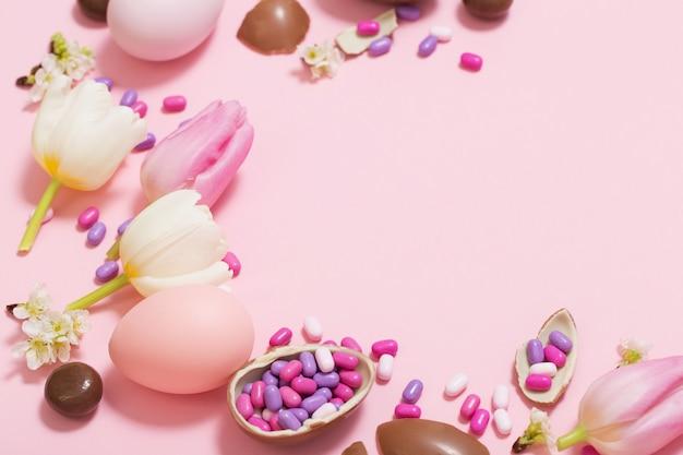 Rosa tisch mit schokoladeneiern und blumen