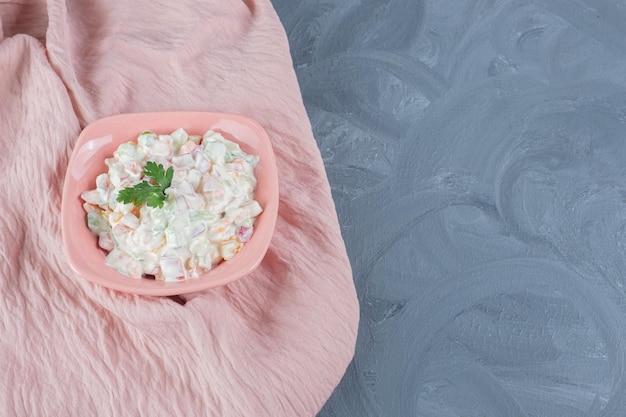 Rosa tischdecke unter einer schüssel oliviersalat auf marmorhintergrund.