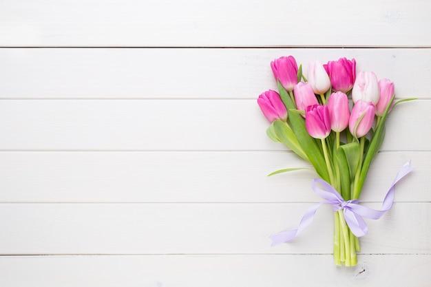 Rosa tulpe auf dem weißen hintergrund. oster- und frühlingsgrußkarte.
