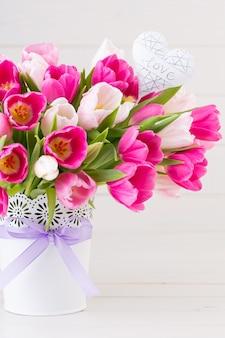 Rosa tulpe auf der weißen oberfläche. oster- und frühlingsgrußkarte.