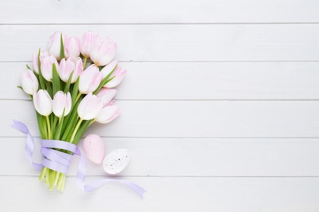 Rosa tulpe auf der weißen oberfläche. osteroberfläche.