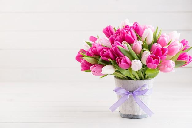 Rosa tulpe auf der weißen oster- und frühlingsgrußkarte.
