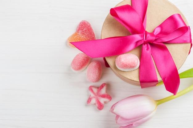 Rosa tulpe und geschenkbox mit rotem band