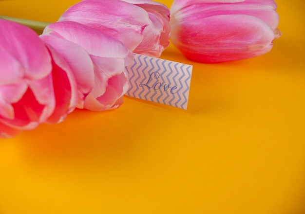 Rosa tulpen auf dem gelben hintergrund mit anmerkungsliebesliebesbrief