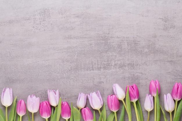 Rosa tulpen auf grauem tisch.