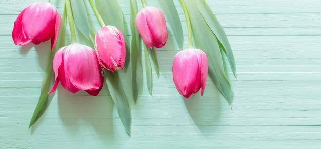 Rosa tulpen auf grünem hölzernem hintergrund
