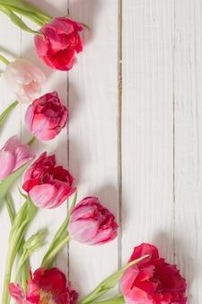 Rosa tulpen auf weißem hölzernem hintergrund