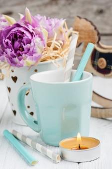 Rosa tulpen, blaue tasse, strohhalme, brennende kerze