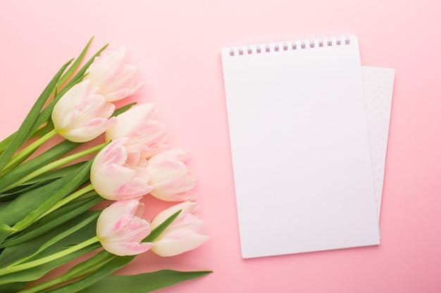 Rosa tulpen des notizbuchs und der frühlingsblume auf dem rosa