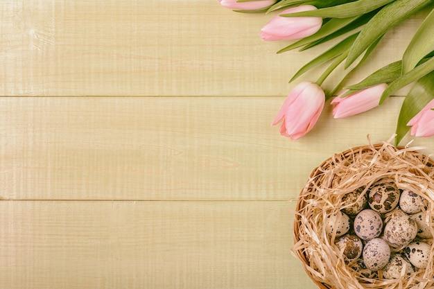 Rosa tulpen des osterhintergrundes auf hölzernem tischwachteleiernest