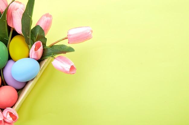 Rosa tulpen in der schachtel und ei ostern auf gelb