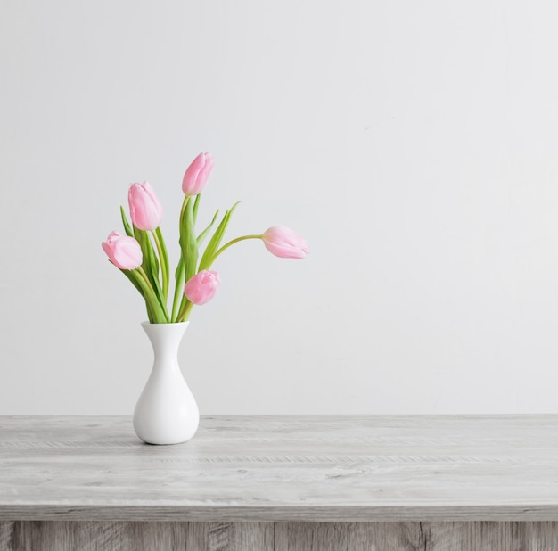 Rosa tulpen in der weißen keramikvase auf holztisch auf weißer hintergrundwand