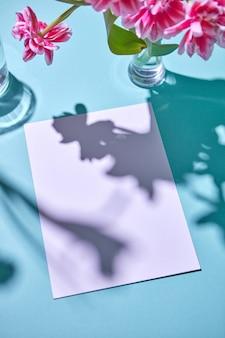 Rosa tulpen in einer glasvase und weißem blattpapier