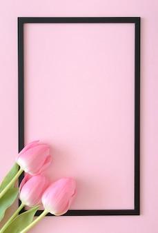 Rosa tulpen kommen aus der ecke auf einem rosa hintergrund mit einem schwarzen rahmen. frühlings-stillleben-konzept. flach liegen.