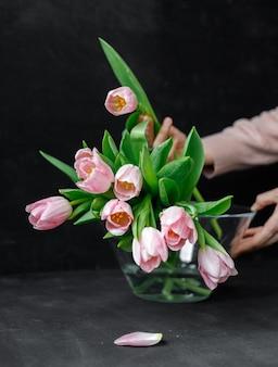 Rosa tulpen mit grünen blättern in einer glasvase eine frau, die tulpen in ihren händen hält florist floristik muttertagsgeschenkstrauß für 8. märzstrauß für ein mädchen auf ihrem geburtstagstrauß von tulpen