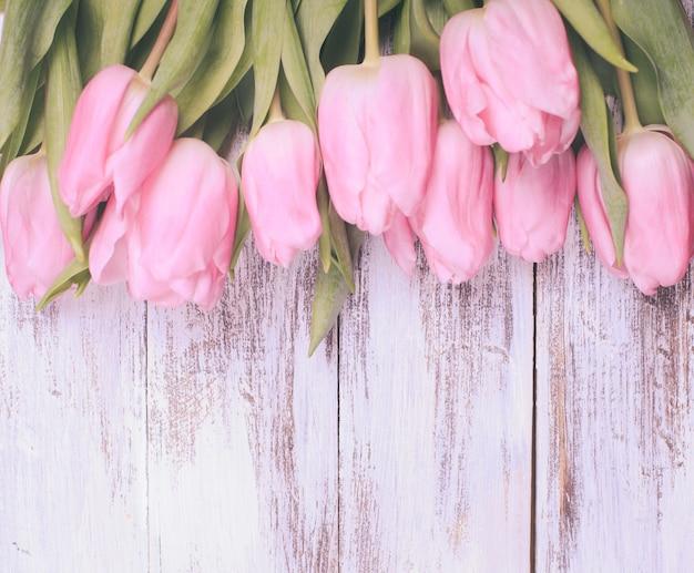 Rosa tulpen über schäbigen weißen holztisch, vintage-retro-stil