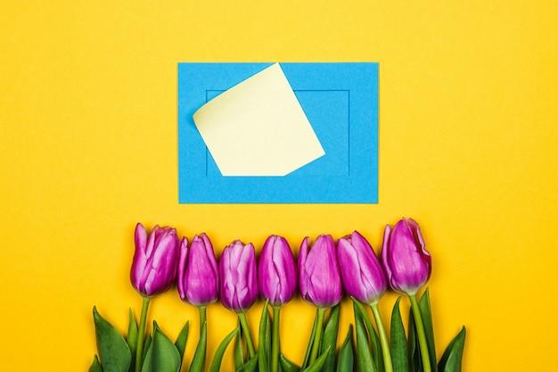 Rosa tulpen und blaue umschlag-osterdekoration. frauentagskarte