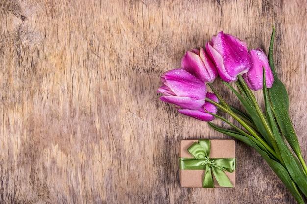 Rosa tulpen und geschenkbox auf hölzernem hintergrund