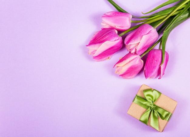 Rosa tulpen und geschenkbox auf rosa hintergrund
