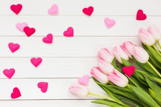 Rosa tulpen und herz auf weißem hölzernem hintergrund. valentinstag hintergrund.