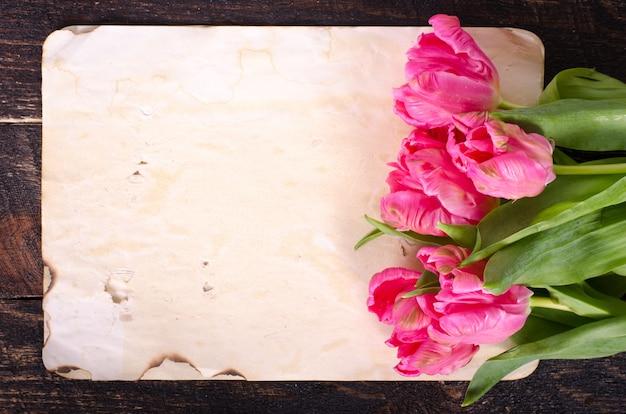 Rosa tulpen und prinzessinschuhe, weinlesepapier auf hölzernem hintergrund.