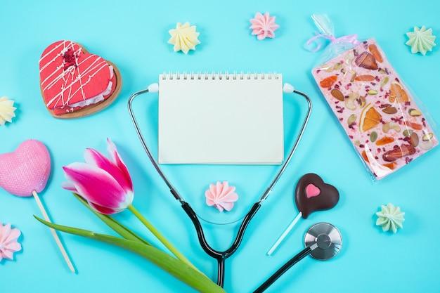 Rosa tulpen und stethoskop mit spiralförmigem notizblock mit glücklichem ärztetagstext darauf