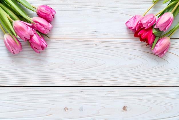 Rosa tulpenblume auf hölzernem hintergrund