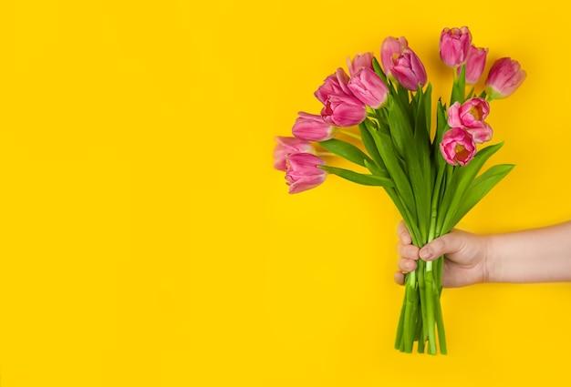 Rosa tulpenblumen in der hand auf gelbem hintergrund konzeptglückwünsche