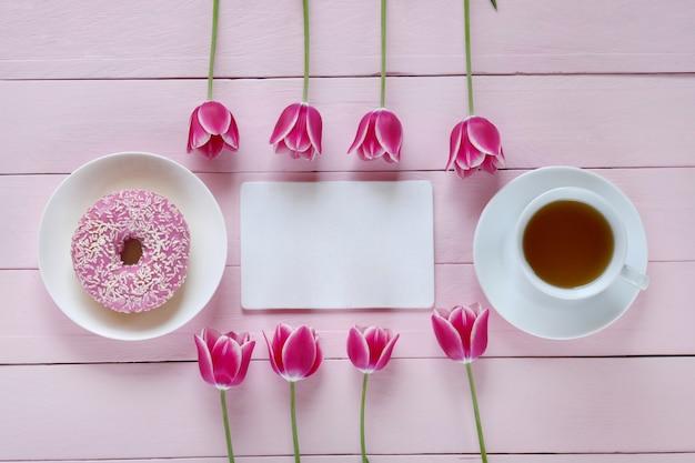 Rosa tulpenblumen, leeres notizbuch, tasse tee und rosa donut auf einem rosa hölzernen hintergrund
